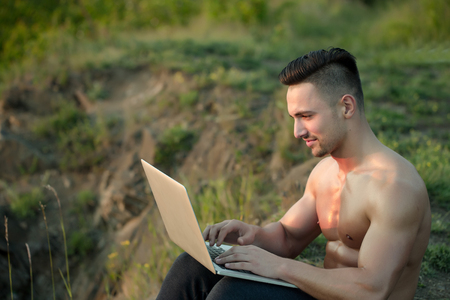 bare chest: Young handsome man with muscular sexy body and bare chest sitting with laptop outdoor sunny day Stock Photo