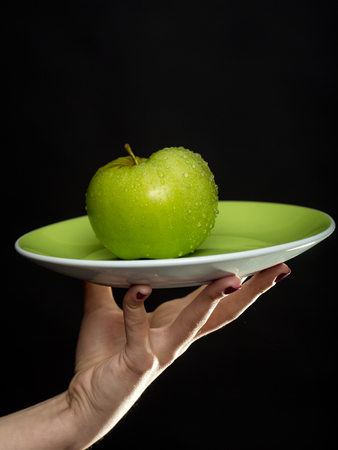 white sleeve: green apple on plate in human hand of young chef in white sleeve on black background