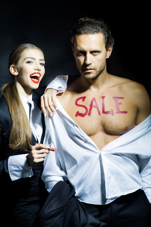 attractive macho: Attractive young couple of pretty girl with red smiling lips and macho man in shirt with bare chest and sale text with lipstick on black background Stock Photo