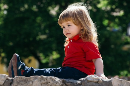 Little adorable boy with long hair on the stone fence