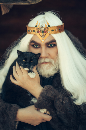 druid: Druid old man with long grey hair and beard with crown in fur coat holds cat on dark background Stock Photo