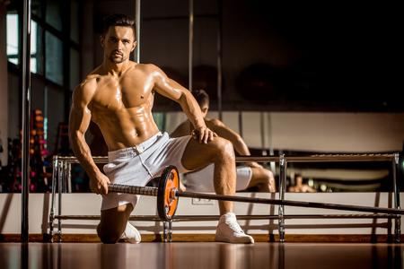 nackte brust: Gut aussehender junger Mann mit sexy muskulösen Körper nass nackten Oberkörper und Brusttraining mit schweren Hantel im Fitness-Studio