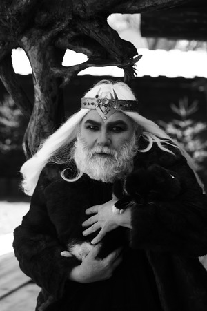 druid: Druid old man with long grey hair and beard with crown in fur coat holds cat black and white on dark wooden background