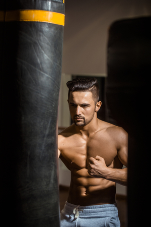punching bag: Handsome young man with sexy muscular body bare torso and chest near punching bag