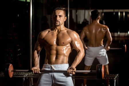 tricep: Handsome young man with sexy muscular wet body bare torso and chest training with heavy barbell in gym Stock Photo