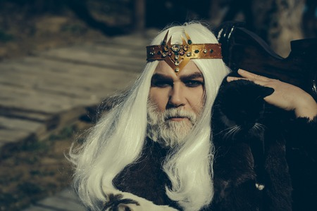 silver hair: Druid old man with long silver hair beard with crown with black cat on shoulder in fur coat on blurred background