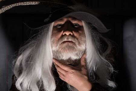 hair feathers: Druid old man with long grey hair and beard in hunter hat with bird feathers face illuminated on dark background Stock Photo