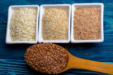 organic flax seed: Organic raw rice crops maize and barley grits in white plates and spoon with linseeds on dark blue background studio