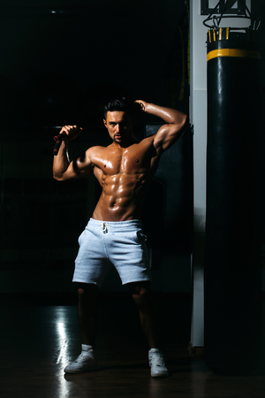 jump rope: Handsome young man with sexy muscular wet body bare torso and chest holding jump rope