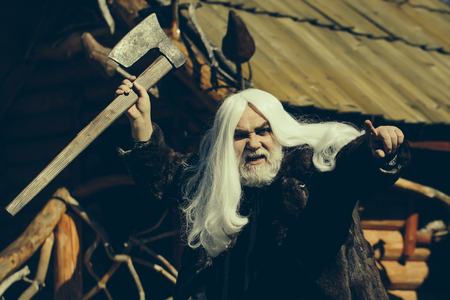 silver hair: Brutal druid old man with long silver hair and beard in fur coat with axe in hand on log house background Stock Photo