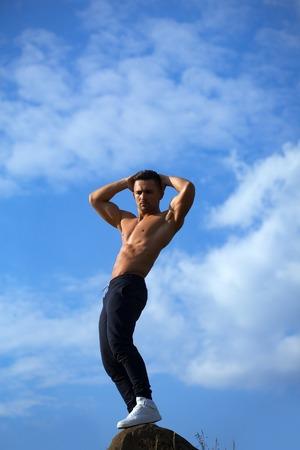 nackte brust: jungen Macho-Mann-Modell Athlet mit muskulösen sexy Körper und nackten Brust am Himmel Hintergrund posiert im Freien