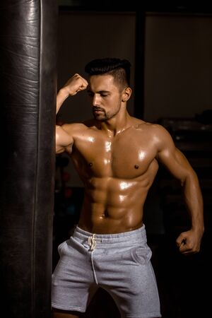 body bag: Handsome young man with sexy muscular body bare torso and chest near punching bag