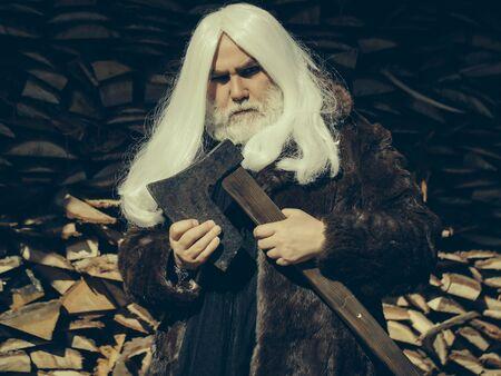 manteau de fourrure: Vieil homme druidique avec de longs cheveux d'argent et la barbe en manteau de fourrure se tient � la hache sur fond woodpile