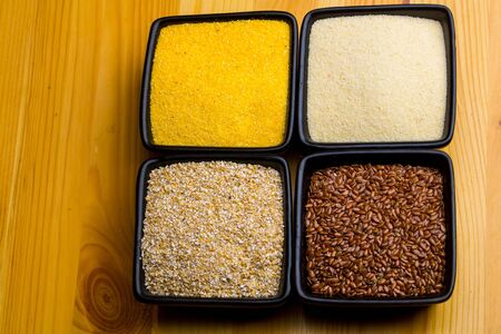 organic flax seed: Raw millet maize rice grits and linseed in black square bowls on wooden background studio Stock Photo