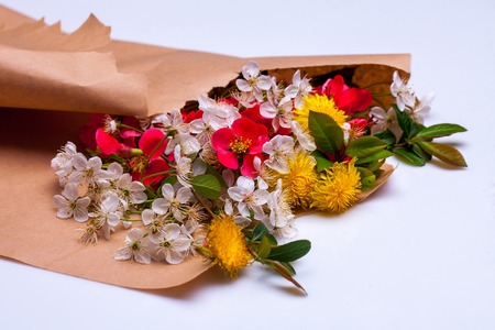 packing paper: Bouquet of spring flowers in brown packing paper isolated on white background