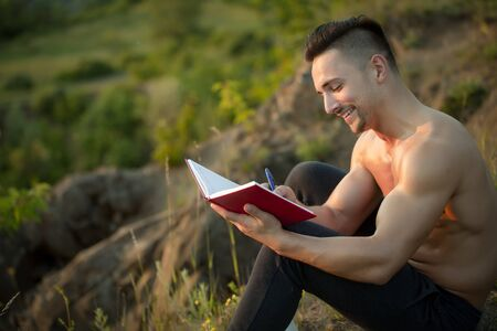 bare chest: Young handsome smiling man with muscular sexy body and bare chest sitting with book outdoor sunny day