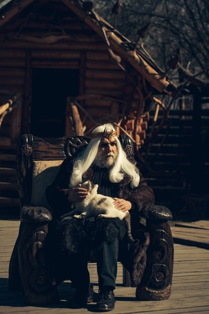 house coat: Druid old man with long grey hair beard with crown in fur coat holds cat and sits in wooden chair on log house background