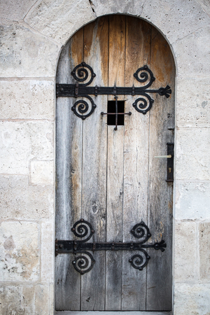 grating: Old wooden faded strong medieval door with metal latches and small grating window on natural background outdoor Stock Photo