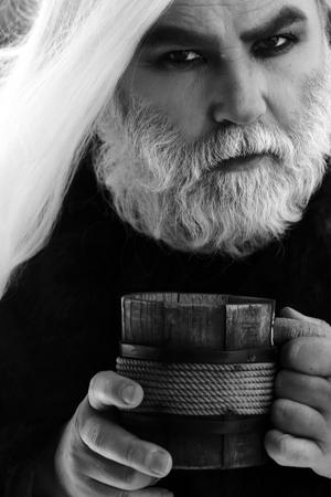 druid: Druid old man with wrinkles long silver beard hair with wooden mug in hands black and white on grey background Stock Photo