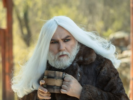 druid: Druid old man with long grey hair and beard in fur coat with wooden mug in hands on blurred background Stock Photo