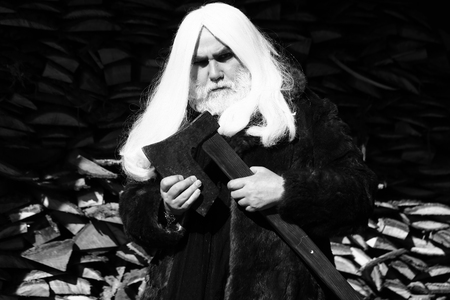 the stands: Old man druid with long silver hair and beard in fur coat stands with axe black and white on woodpile background Stock Photo