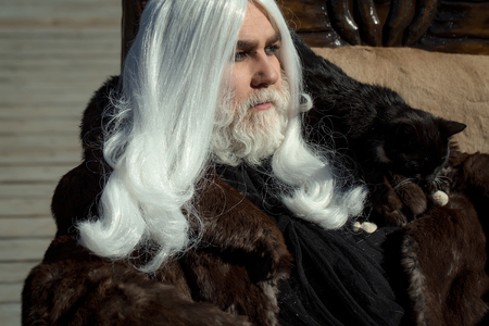 druid: Druid old man with long silver hair beard with black cat on shoulder in fur coat on grey background