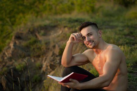 nackte brust: Junger stattlicher lächelnder Mann mit dem muskulösen sexy Körper und nackte Brust mit Buch im Freien sonnigen Tag sitzt Lizenzfreie Bilder