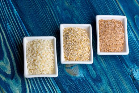 granule: Square white plates with raw rice grain maize and millet grits on dark blue wooden background studio