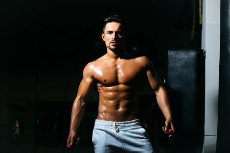 saltar la cuerda: apuesto joven con sexy cuerpo mojado torso desnudo muscular y la celebración de saltar la cuerda en el pecho