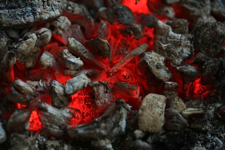 comfortableness: open fire with hot ash and charcoal burning with bright orange flame as abstract background Stock Photo