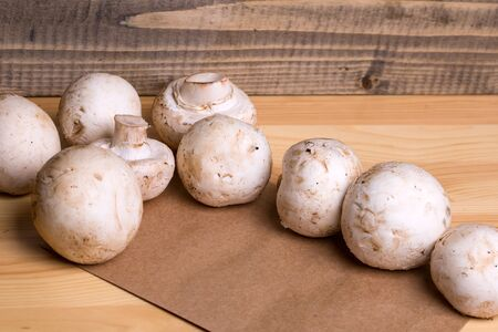 button mushrooms: Fresh champignons unpeeled white button mushrooms on brown packing paper on wooden background