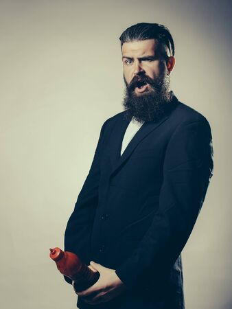 ketchup bottle: Handsome young man with long beard and moustache in black jacket holding red plastic ketchup bottle in studio on grey background