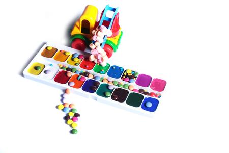 paletas de caramelo: Conjunto de pinturas de acuarela con pincel en paleta sobre fondo blanco closeup con dulces pequeñas en coche de juguete de plástico, copia espacio
