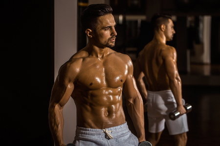 Handsome young man with muscular wet body bare torso and chest training with heavy dumbbell in gym