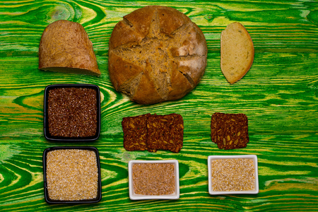 flax seeds: Loaf of homemade bread slices flax seeds and organic grain in bowls on green wooden background