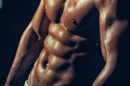 sixpack: muscular male torso six packs on wet body of athletic man training with bare chest and strong biceps on hands, closeup