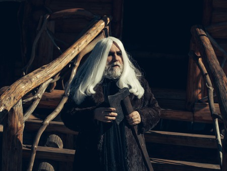 house coat: Old man druid with long silver hair and beard in fur coat stands with axe on log house background