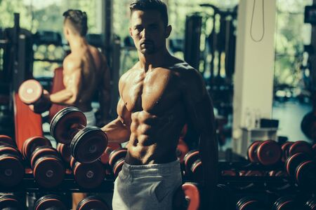 Handsome young man with muscular wet body torso and chest training with heavy dumbbell in gym
