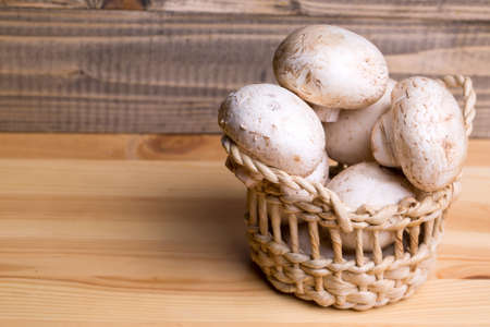 button mushrooms: Fresh champignons unpeeled white button mushrooms in basket on wooden background
