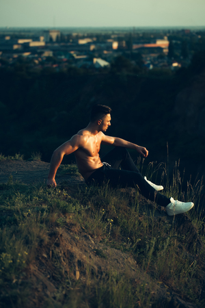 bare chest: young macho man model athlete with muscular body and wet bare chest outdoor on hill with city landscape