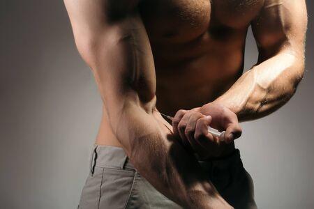 nackte brust: Nackte Brust und muskulösen männlichen Arm des jungen Mannes mit großen Bizeps und Spritze mit dünnen Nadel als Symbol der Medizin anabole oder Drogen Injektion machen Lizenzfreie Bilder