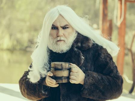 manteau de fourrure: Druid vieil homme avec de longs cheveux gris et barbe en manteau de fourrure avec la tasse en bois dans les mains sur fond flou