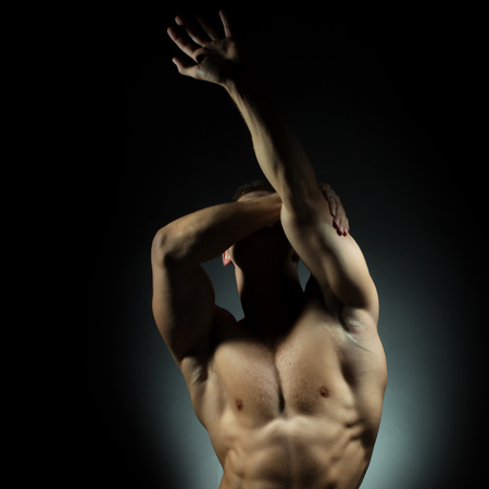 bare chest: muscular male torso of athlete bodybuilder posing in power with veins on hands and bare chest on grey background
