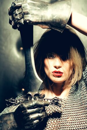 chain armour: young pretty female warrior in silver chain armour and iron gloves with long hair and red lips holding ancient sword, closeup Stock Photo