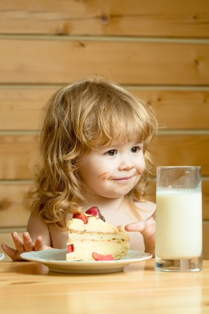 long hair boy: cute little boy child with long blonde hair eating tasty creamy pie or cake with red strawberry fruit and glass of yogurt