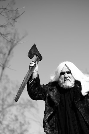 silver hair: Brutal druid old man with long silver hair and beard in fur coat with axe in hand black and white on grey sky background