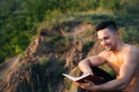 nackte brust: Junger stattlicher l�chelnder Mann mit muskul�sen K�rper und nackte Brust mit Buch im Freien sonnigen Tag sitzt