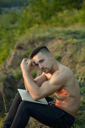 bare chest: Young handsome man with muscular body and bare chest sitting with laptop outdoor sunny day