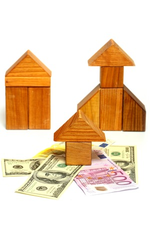 morgage: wooden toy house over euro and dollar banknote isolated on white background. property management concept.