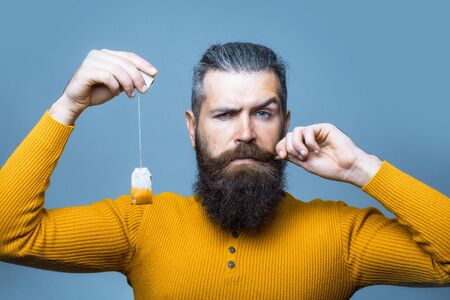 tea bag: handsome bearded man with long lush beard and moustache on serious face holding tea bag in yellow shirt in studio on blue background